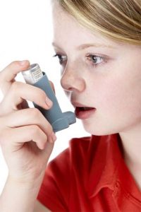 Teenage girl using asthma inhaler